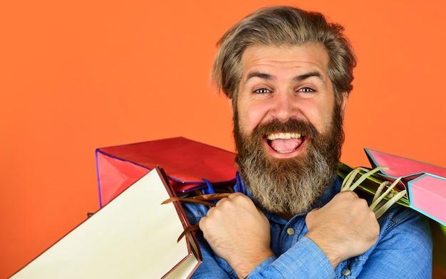 Facile e veloce. uomo positivo che gode dello shopping. propria attività. l'uomo barbuto tiene il sacchetto di carta. regali. felice l'uomo shopping online. pantaloni a vita bassa estremamente felici che fanno acquisti al negozio di elettronica.