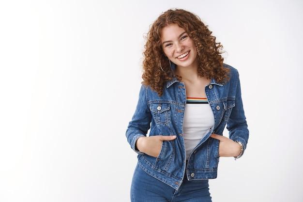 Facile affascinante amichevole giovane ragazza adolescente rossa con lentiggini brufoli indossare giacca di jeans tenere le mani tasche ridere ampiamente divertirsi umore positivo in piedi sfondo bianco