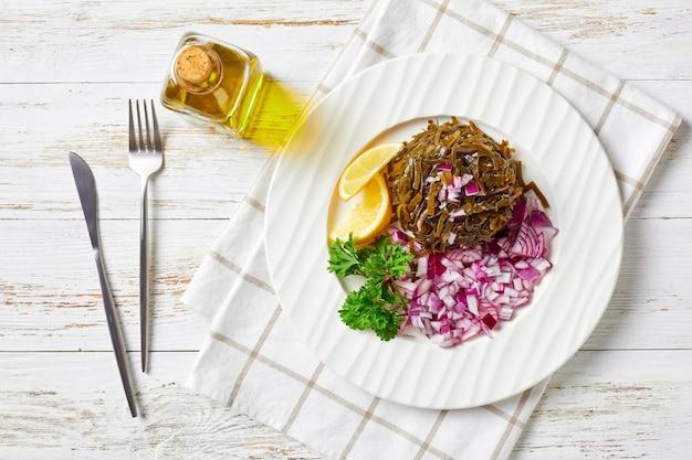 Facile insalata wakame marinata con cipolla rossa a dadini e spicchi di limone, su un piatto bianco con prezzemolo fresco, cosparsa di semi di sesamo, fiocchi di peperoncino sulla parte superiore su un tavolo di legno, vista dall'alto, piatto lay