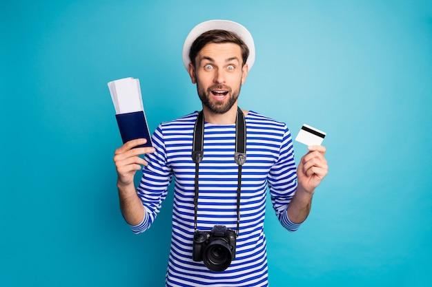 Pagamento facile! foto di pazzo ragazzo scioccato fotografo tenere fotocamera digitale viaggiatore acquista biglietti con l'aiuto di carta di credito indossare camicia da marinaio a strisce giubbotto cappuccio isolato colore blu
