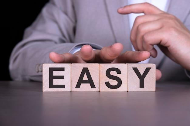 Facile, la parola è scritta su cubi di legno, blocchi sullo sfondo di un uomo