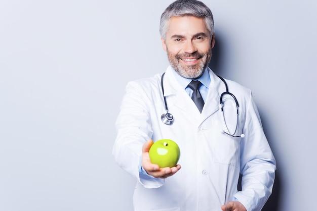 Mangiare sano! medico maturo allegro nel darti una mela verde e sorridere mentre si trova in piedi su uno sfondo grigio