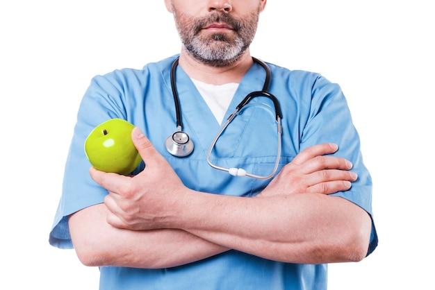 Mangiare sano! primo piano del chirurgo in uniforme blu che tiene mela verde mentre sta in piedi isolato su bianco