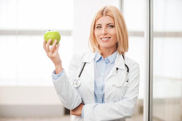 Mangiare sano! fiduciosa dottoressa in uniforme bianca che tiene in mano una mela verde e sorride mentre si appoggia alla parete di vetro