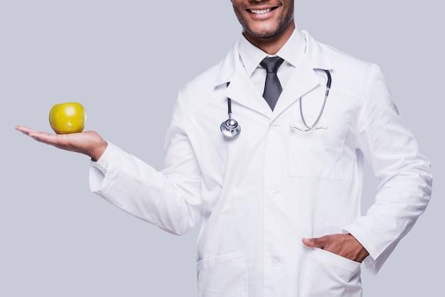 Mangiare sano! immagine ritagliata del medico africano che allunga la mela verde