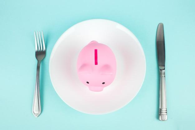 Mangia risparmi, spese alimentari. vista ravvicinata del salvadanaio con una forchetta e un coltello sul piatto bianco.
