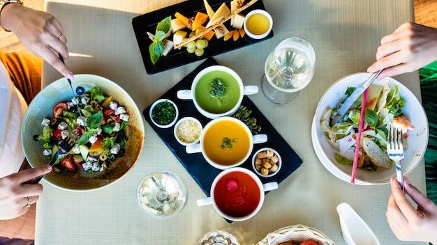 Mangiare insalata di pollo con diverse zuppe sul tavolo