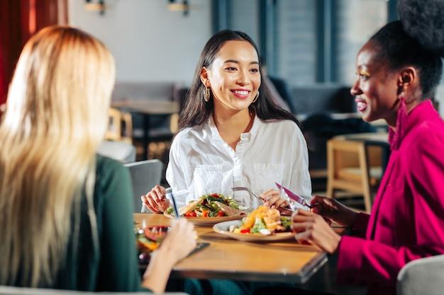Mangiare deliziose insalate tre migliori amici felici che mangiano deliziose insalate nel loro ristorante preferito