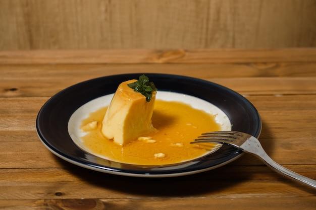 Mangiare il delizioso dolce tipico argentino e sudamericano chiamato flan con caramello. la mano del commensale viene osservata. concetto di mangiare sano e naturale.
