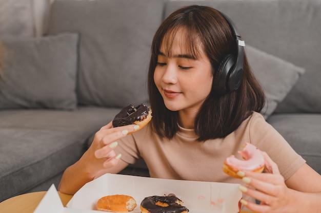 Mangiare ciambella durante l'asporto e la consegna. fast food da asporto a casa. stile di vita della donna asiatica in soggiorno. distanziamento sociale e nuova normalità.