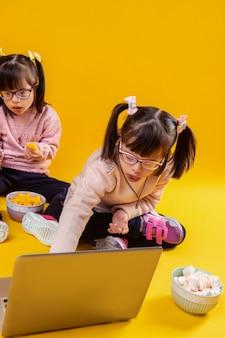 Mangiare dalla ciotola. due sorelle con disturbo mentale che giocano con il laptop mentre sono circondate da snack
