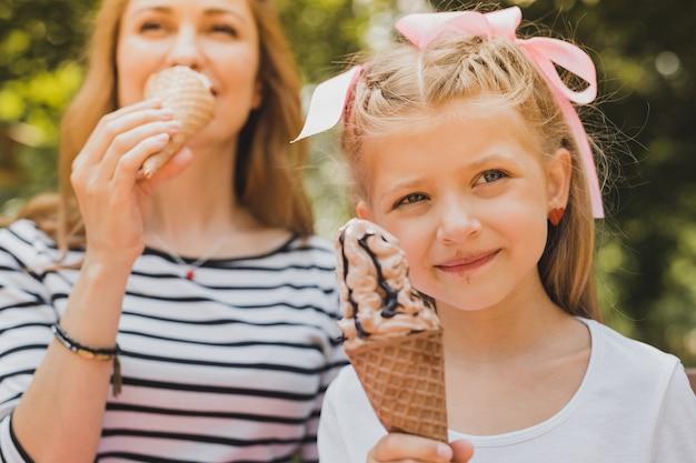 Mangiando un gelato. figlia dagli occhi azzurri sorridente dai capelli biondi con stile di capelli carino che mangia il gelato