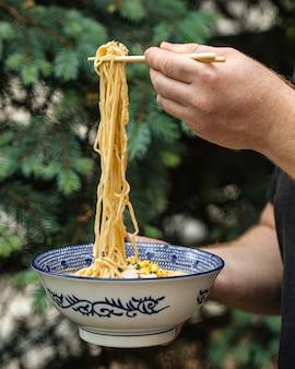 Mangiare la zuppa di spaghetti ramen giapponesi con le bacchette