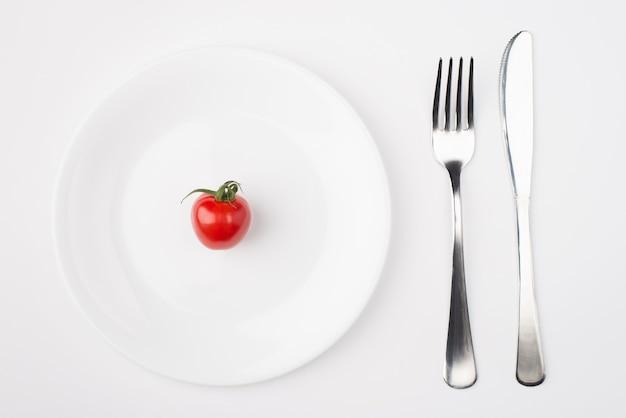 Mangiare su un concetto a basso contenuto calorico. vista dall'alto sopra la foto di un piatto con un singolo pomodoro con forchetta e coltello posizionati sul lato destro isolato su sfondo bianco