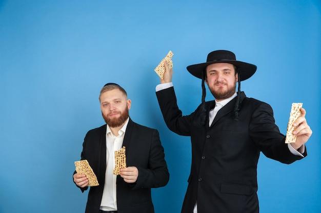 Mangiare matzah, invitante. ritratto di giovani uomini ebrei ortodossi isolati sulla parete blu. purim, affari, festival, vacanza, celebrazione pesach o pasqua ebraica, ebraismo, concetto di religione.