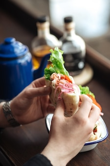 Mangiare sandwich di pita con verdure e pesce affumicato