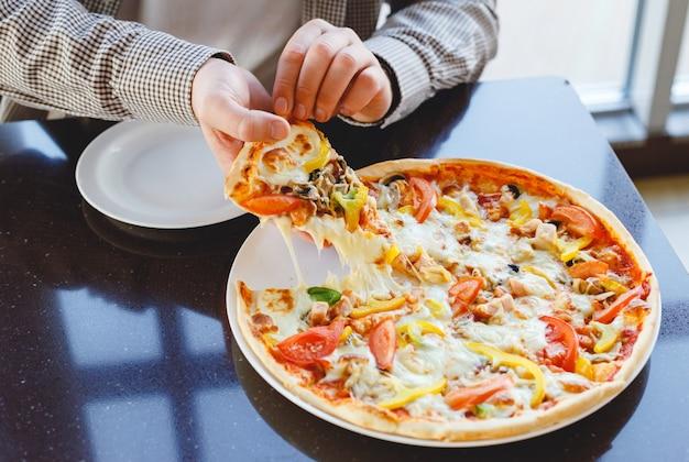 Mangiare la pizza a casa. consegna deliziosa della pizza. l'uomo caucasico prende il pezzo di deliziosa pizza italiana con mozzarella a casa o in bar, ristorante. pizza fast food.