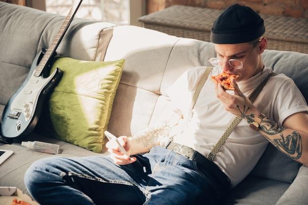 Mangiare pizza. uomo che mangia pizza sul divano mentre controlla il cellulare.