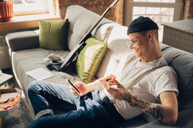 Mangiare pizza. uomo che studia a casa durante i corsi online, scuola intelligente. ottenere lezioni o professione mentre si è isolati, quarantena contro la diffusione del coronavirus. utilizzando laptop, smartphone, cuffie.