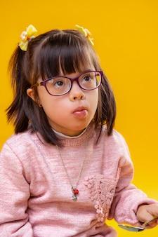 Mangiare spuntini. attenta bambina con gli occhi marroni con sindrome di down e acconciatura scura funky