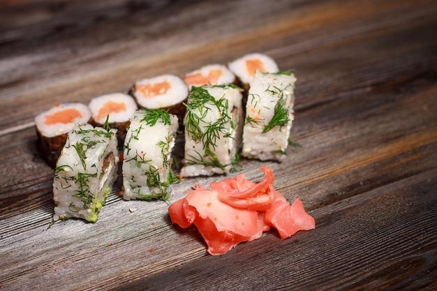 Mangiare sushi roll delicatezza cibo dieta gourmet cucina asiatica sfondo di legno Foto Premium