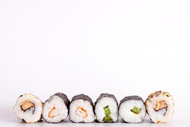 Mangiare sushi con le bacchette. rotolo di sushi cibo giapponese nel ristorante isolato su sfondo bianco.