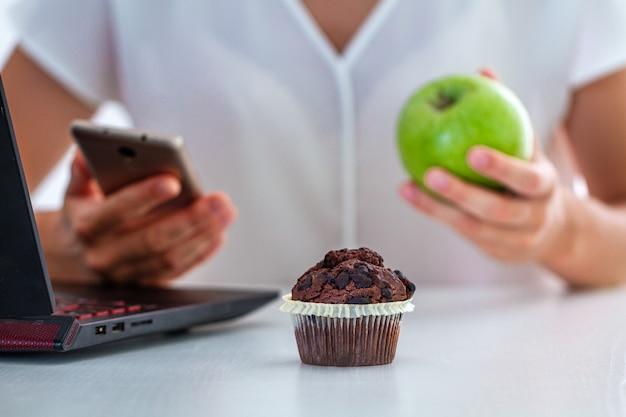 Mangiare al lavoro, pausa pranzo in ufficio. la donna di affari mangia il muffin al cioccolato e alla mela mentre lavora al telefono e al computer portatile