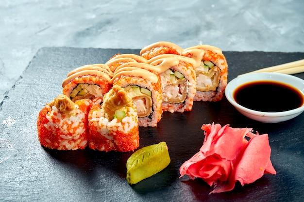 Rotolo di sushi ebi con gamberi in tempura e caviale tobiko su sfondo nero ardesia. messa a fuoco selettiva