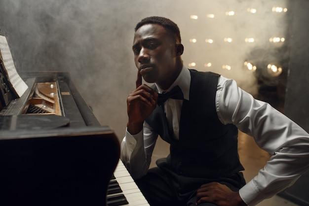 Il musicista del pianoforte a coda ebano posa sul palco