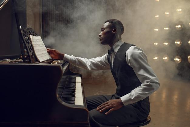 Pianista ebano, interprete jazz sul palco con riflettori. musicista posa allo strumento musicale prima del concerto