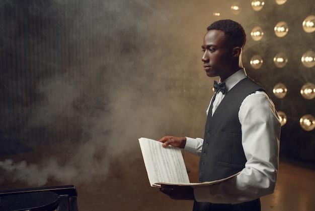 Pianista in ebano con taccuino musicale sul palco