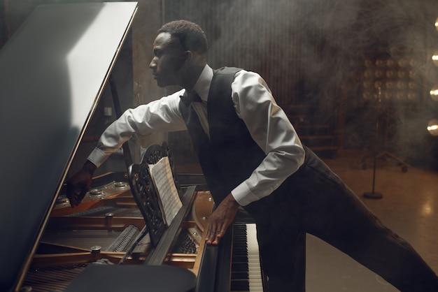 Giocatore di ebano sintonizzazione pianoforte a coda sul palco con faretti. performer pone allo strumento musicale prima del concerto
