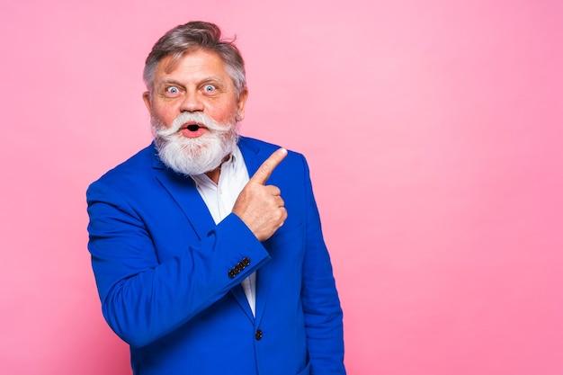 Uomo maggiore eccentrico con blazer blu sulla parete rosa