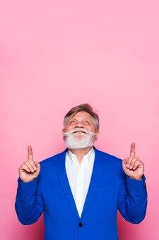 Uomo maggiore eccentrico con blazer blu rivolto verso l'alto sulla parete rosa