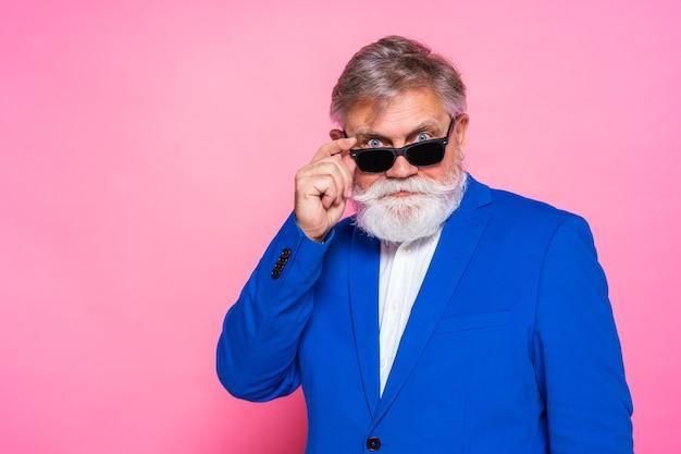Uomo maggiore eccentrico con giacca blu e occhiali da sole sulla parete rosa