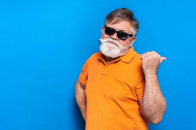Uomo maggiore eccentrico con ritratto di espressione divertente sulla parete blu