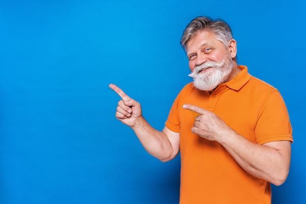 Uomo maggiore eccentrico con ritratto di espressione divertente isolato sull'azzurro