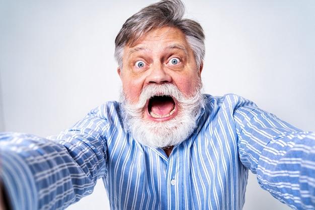 Uomo maggiore eccentrico con ritratto di espressione divertente isolato su bianco