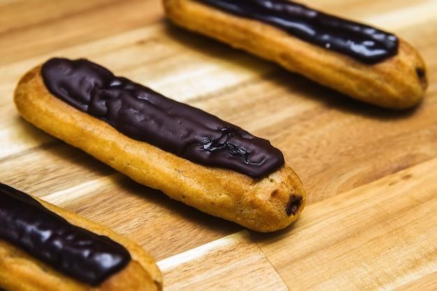 Eclair torta cremosa croccante con cioccolato fondente isolato su superficie di legno