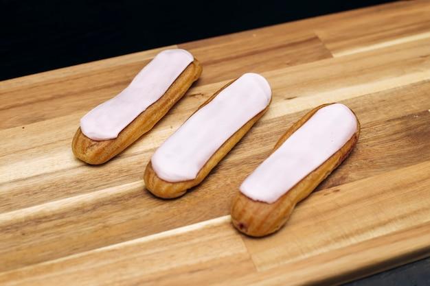 Eclair torta cremosa croccante con cioccolato bianco isolato su superficie di legno