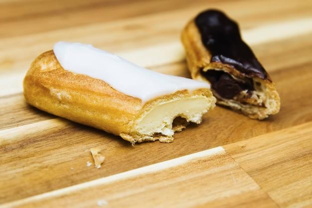 Eclair torta cremosa croccante con cioccolato bianco e fondente isolato su superficie di legno