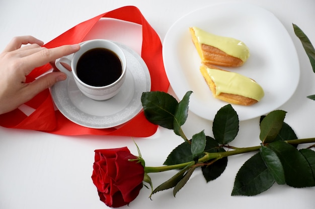 Eclair su un piatto bianco, una rosa rossa e una tazza di caffè. colazione di san valentino.