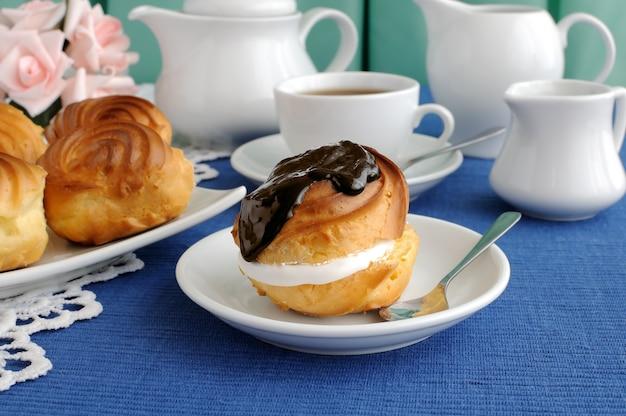 Eclair con il primo piano del cioccolato su un piatto con una tazza di caffè