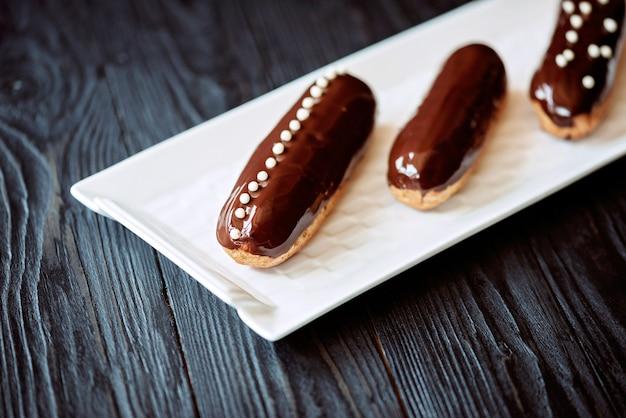Eclairs con glassa al cioccolato fondente e gocce in un piatto bianco su sfondo scuro