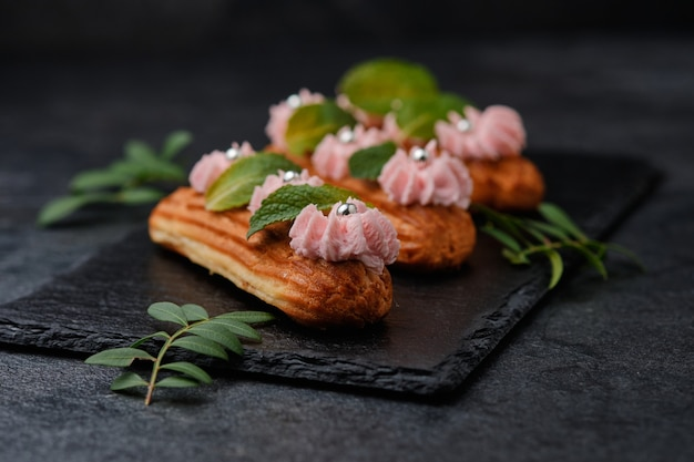 Eclairs con crema rosa, decorati con foglie di menta. dessert su un piatto di ardesia nera. torte su uno sfondo scuro.
