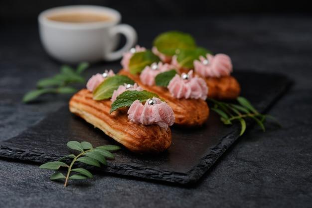 Eclairs con crema rosa, decorati con foglie di menta. dessert su un piatto di ardesia nera. torte ed espresso su uno sfondo scuro.
