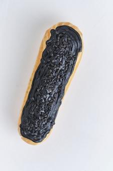 Eclair con crema al pistacchio e glassa nera. torte decorate con rametti di timo. dessert sul tavolo da cucina bianco.