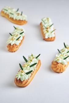 Eclairs con crema al pistacchio e ripieno di lamponi, guarniti con granella di pistacchio e rosmarino.