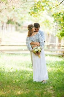 Eclettica coppia rustica in abiti da sposa sullo sfondo della natura