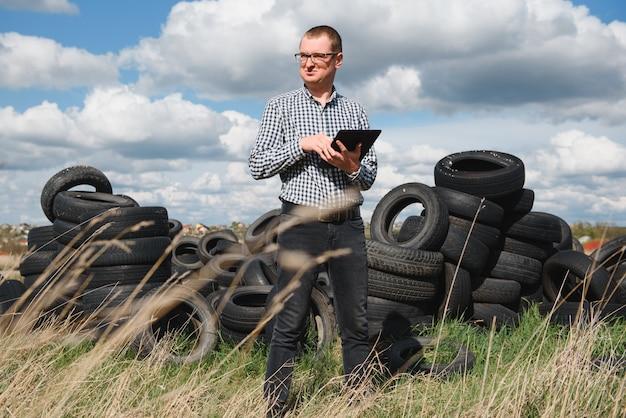 L'eco-attivista presso la discarica di pneumatici per auto usate calcola il danno ambientale